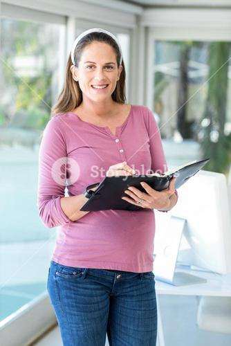 Portrait of pregnant businesswoman with diary