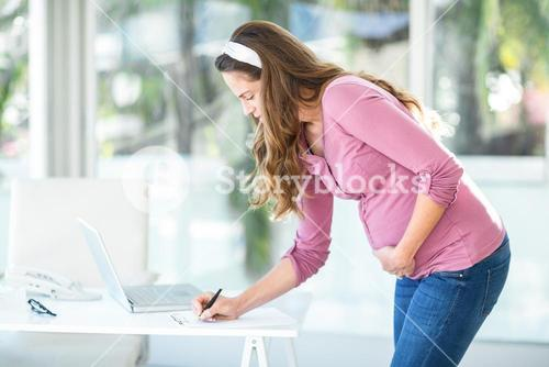 Businesswoman writing note on paper