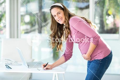 Portrait of businesswoman writing note