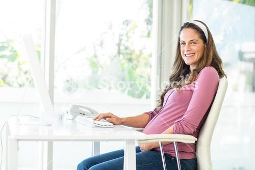 Portrait of happy businesswoman working at computer