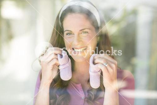 Portrait of happy woman with baby shoes