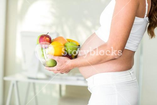 Side view of woman holding fruit bowl