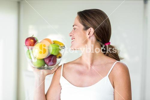 Happy woman looking at fruit bowl