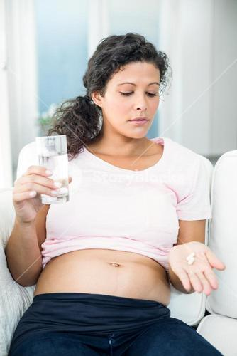 Pregnant woman taking pill at home