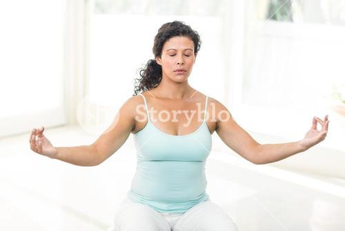 Pregnant woman sitting with eyes closed on exercise ball
