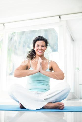 Pregnant woman sitting on exercise mat with joined hands