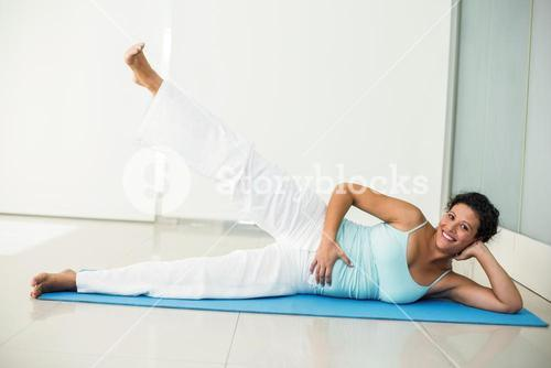 Happy pregnant woman exercising at home