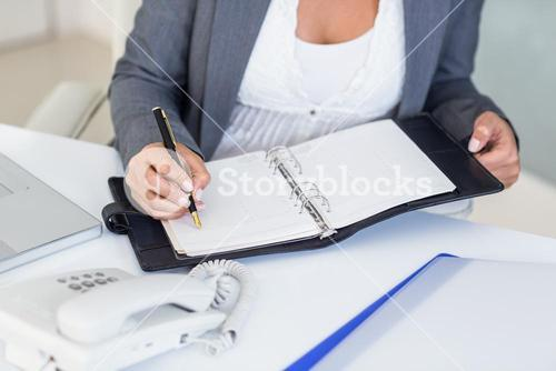 Businesswoman writing on book