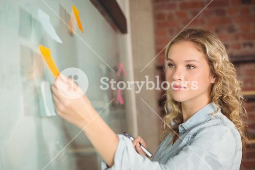 Beautiful businesswoman sticking notes on board in office