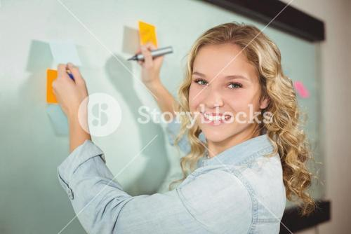 Portrait of beautiful woman holding sticky note while writing on glass board