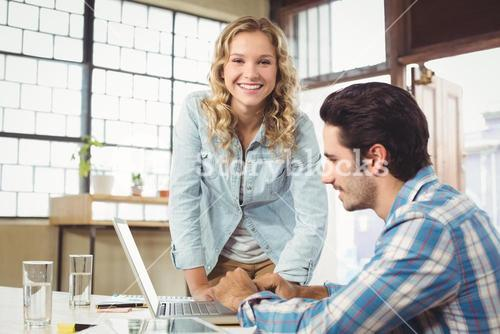 Portrait of woman helping colleague