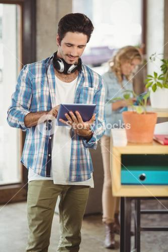 Happy businessman holding digital tablet in creative office