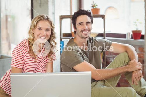 Portrait of happy business people using computer in office