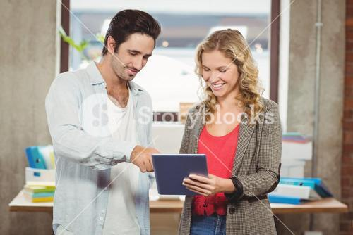 Business people pointing towards digital tablet in office