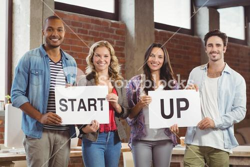 Portrait of smiling business people showing card with start up text in bright office