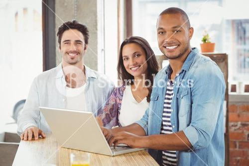 Portrait of smiling business people using laptop in office