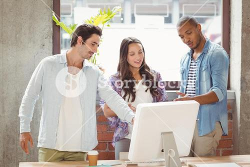 Business people pointing towards laptop in office