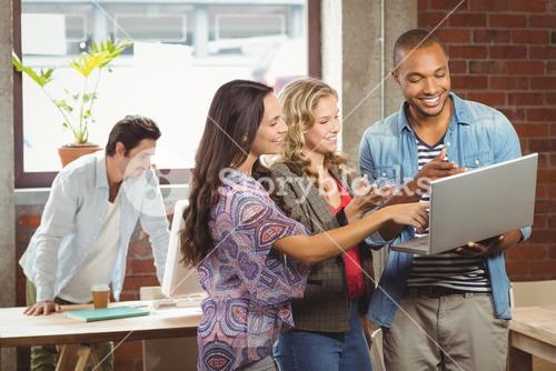 Smiling business people pointing towards laptop