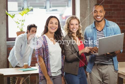 Portrait of smiling business people pointing towards laptop