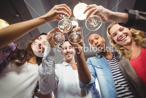 Low angle portrait of happy colleagues toasting with champagne in office