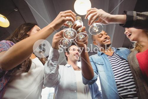 Low angle view of happy colleagues toasting with champagne