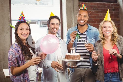 Portrait of casual business people celebrating birthday in office