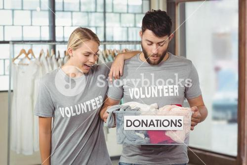 Volunteers looking at clothes in box