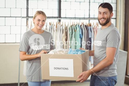 Portrait of smiling volunteer holding clothes donation box