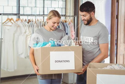 Man and woman volunteers with box standing in office