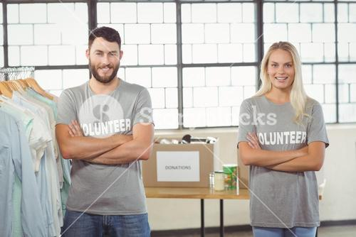 Portrait of volunteers with arms crossed standing by clothes rack