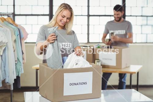 Woman separating clothes from donation box