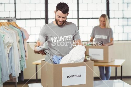 Smiling man separating clothes from donation box