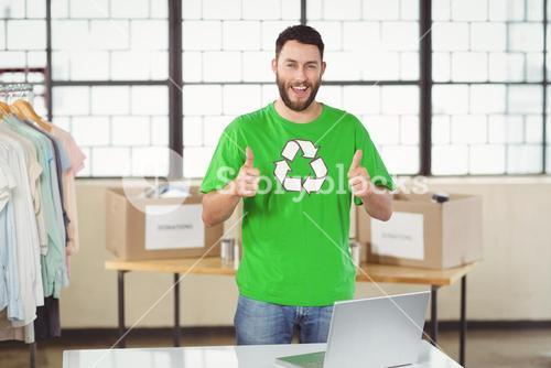 Portrait of happy man in recycling symbol tshirt showing thumbs up