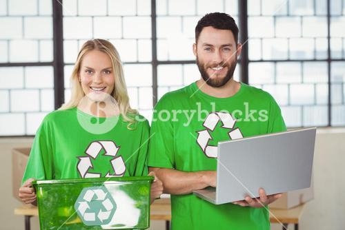 Portrait of smiling volunteers in recycling symbol tshirts