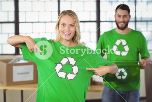 Portrait of woman pointing towards recycling symbol on tshirts