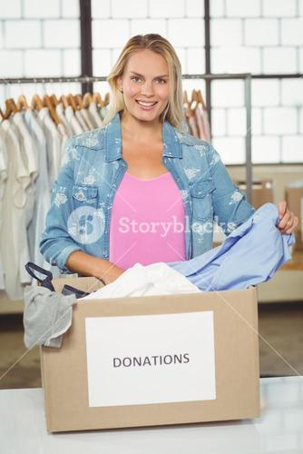 Portrait of woman separating clothes from donation box in office