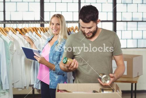 Man separating products while woman holding digital tablet