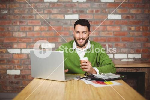 Portrait of businessman holding coffee in office