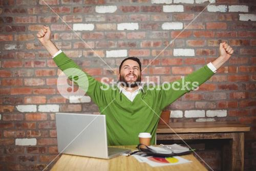 Businessman with arms raised in office