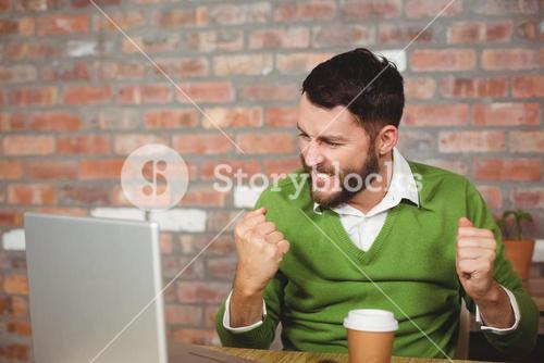 Excited businessman clenching fist in office