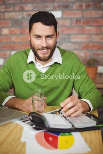 Portrait of smiling businessman writing in diary