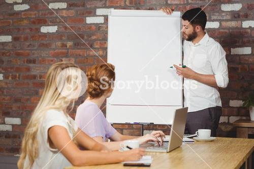 Businessman briefing over whiteboard to colleagues