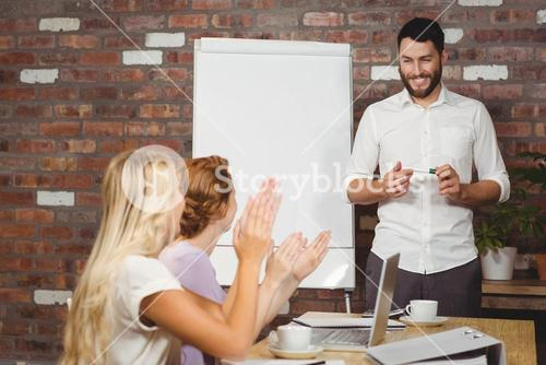 Women praising male colleague during presentation