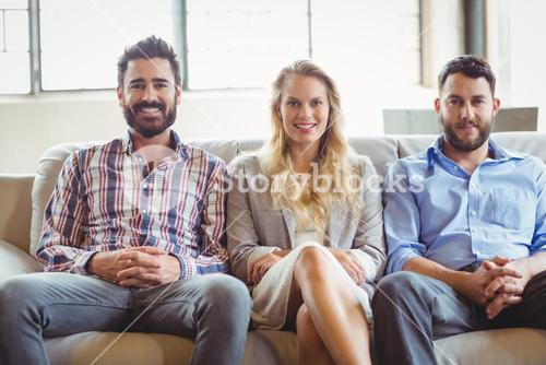 Portrait of happy business people sitting on sofa