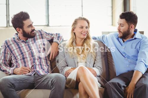Happy business people discussing while sitting on sofa