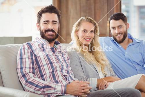 Portrait of happy colleagues sitting on sofa