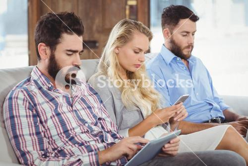 Business people using technologies while sitting on sofa