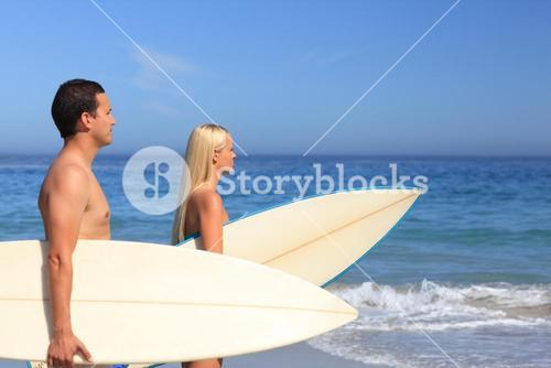 Lovers with their surfboards