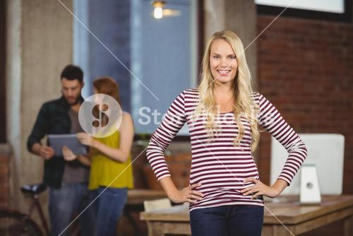 Portrait of happy woman with hands on hip