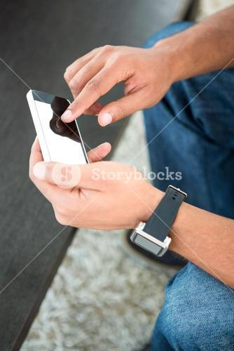 High angle view of man scrolling on mobile phone